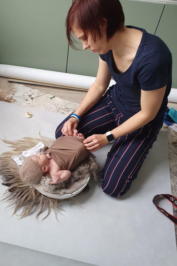 een foto van mij aan het werk met de baby tijdens een newbornshoot op locatie