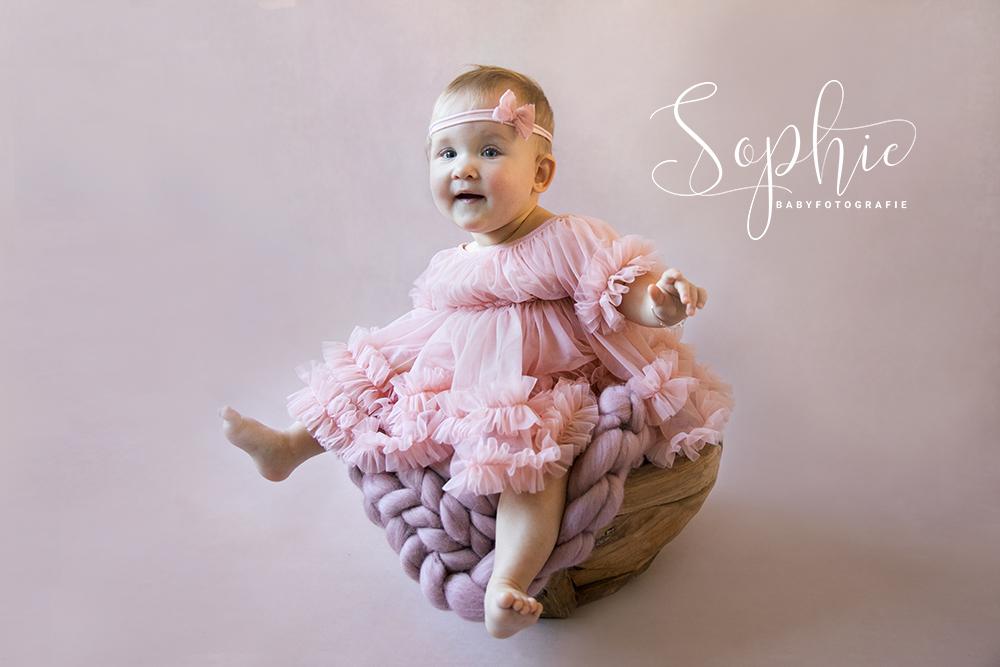 een foto van een sitter in een roze styling tijdens een babyshoot op locatie