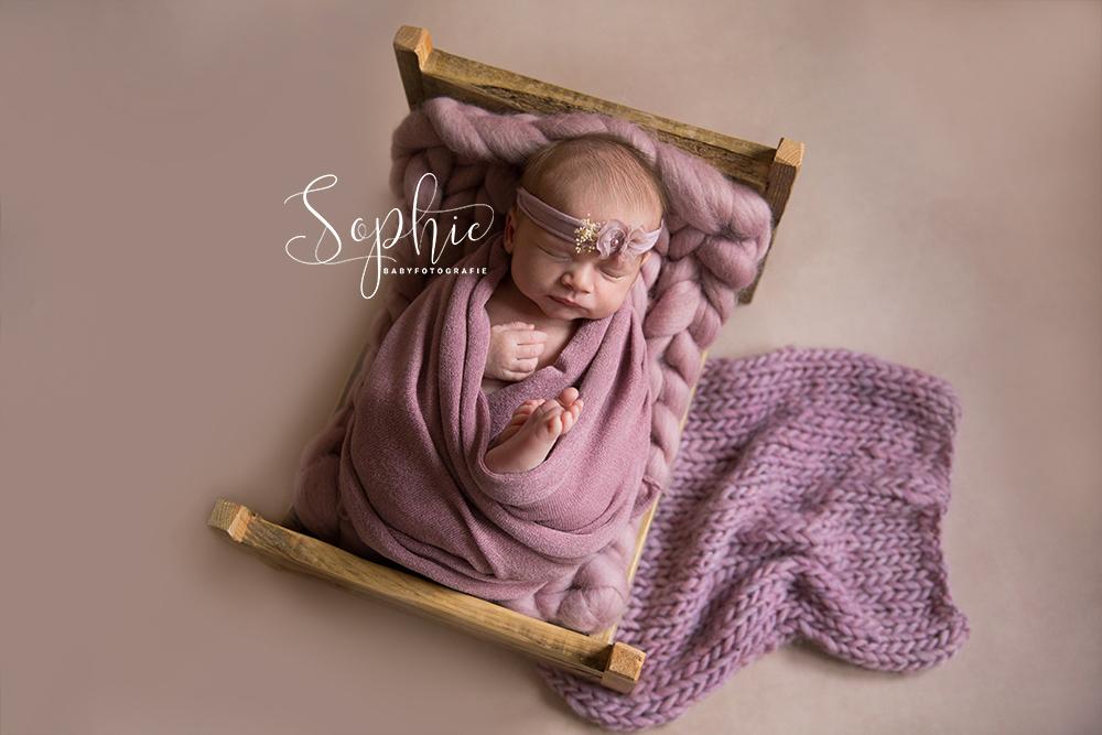 een foto van een diep slapend meisje in een roze styling tijdens een newbornshoot