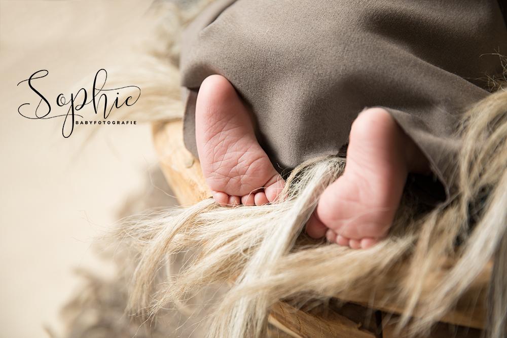 een foto van een slapende newborn in het grijs bruin waarbij we de voetjes zien