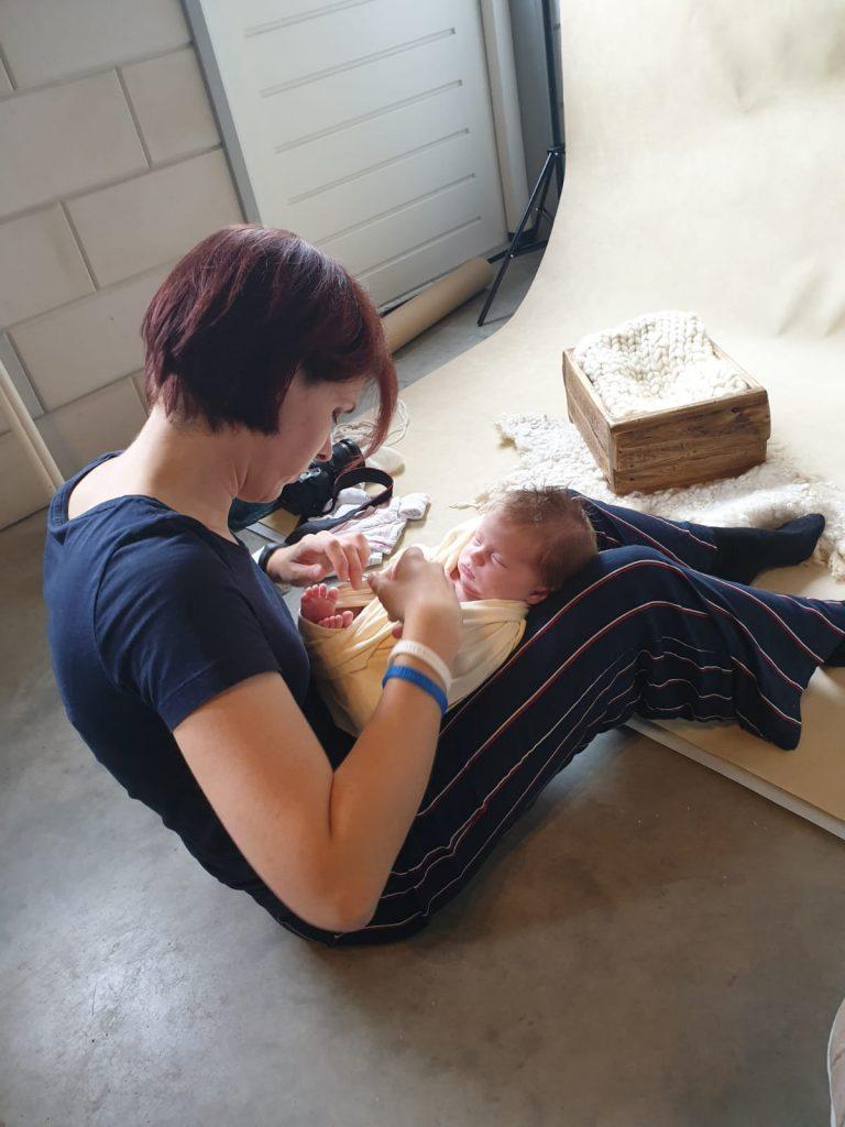 een foto waarop ik de slapende newborn aan het inpakken ben ter voorbereiding op de newbornshoot