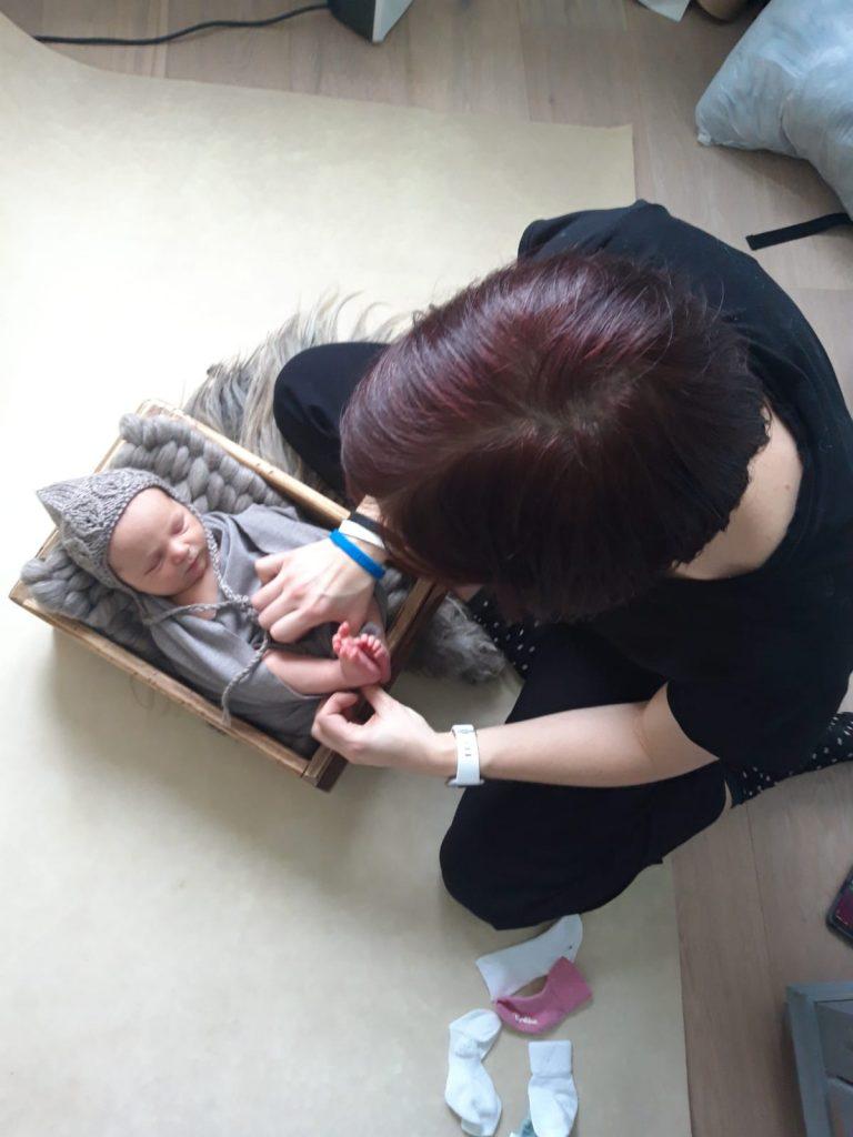 een foto van mij terwijl ik de newborn netjes leg voor de newbornshoot op locatie