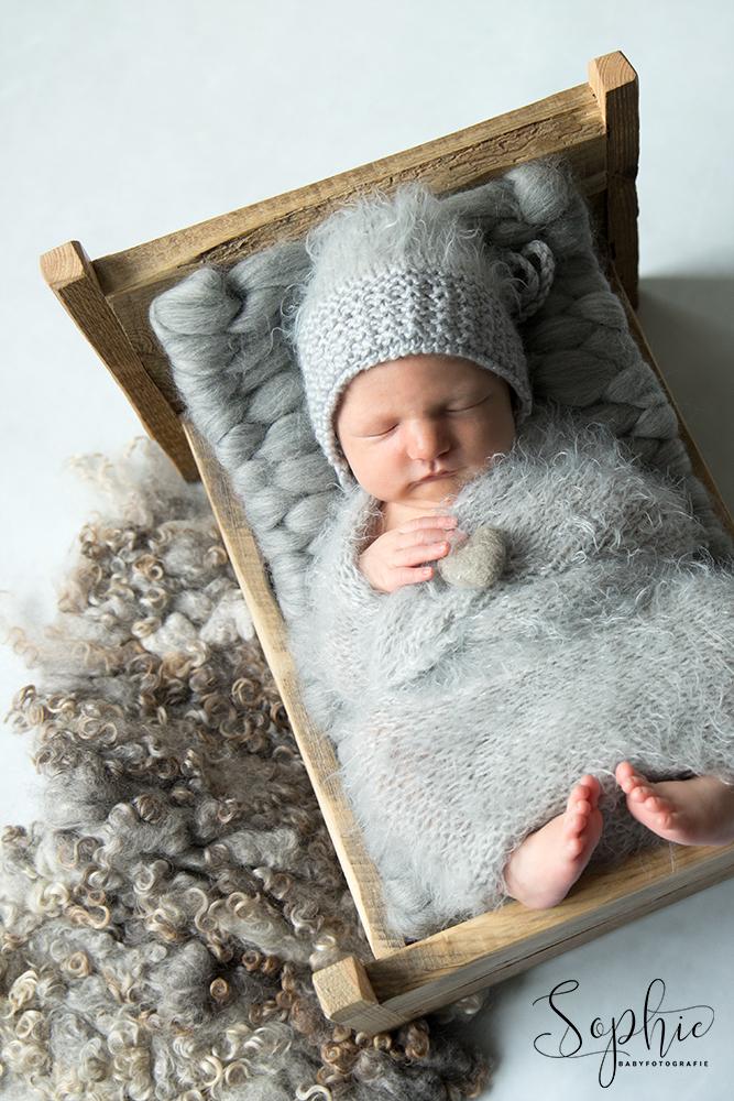 een foto van een newborn in het bekendje bedje