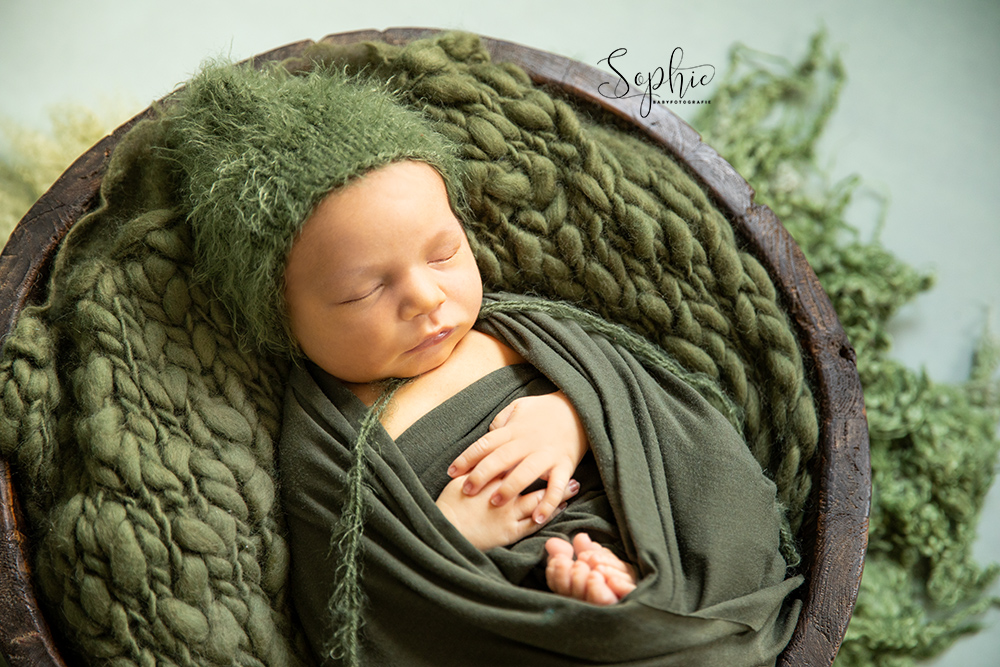 een foto van een newborn in het groen tijdens een newbornshoot