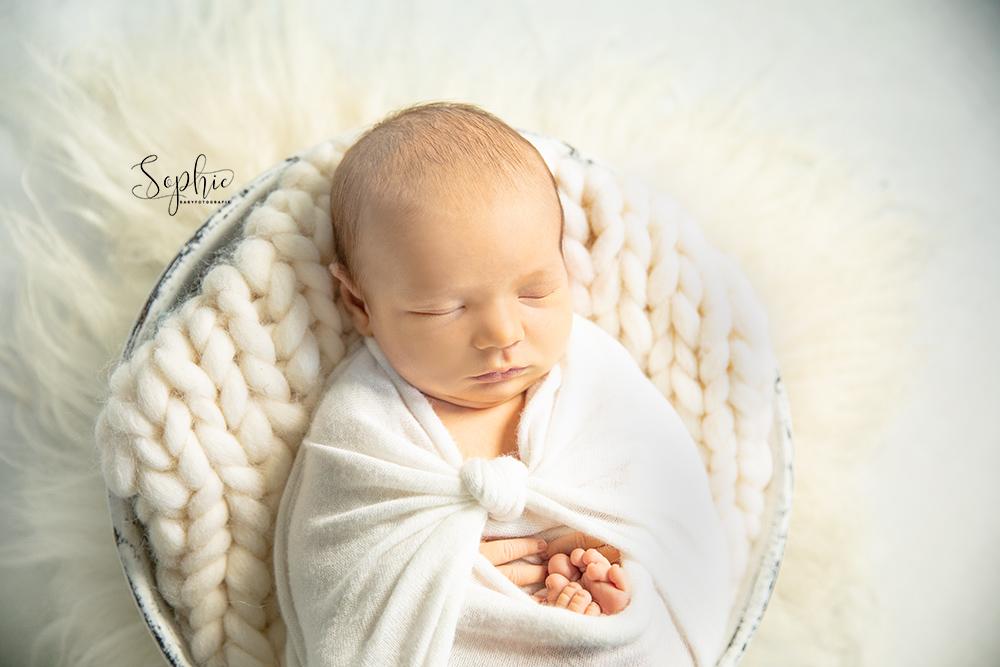 een foto van een newborn in het wit tijdens een newbornshoot