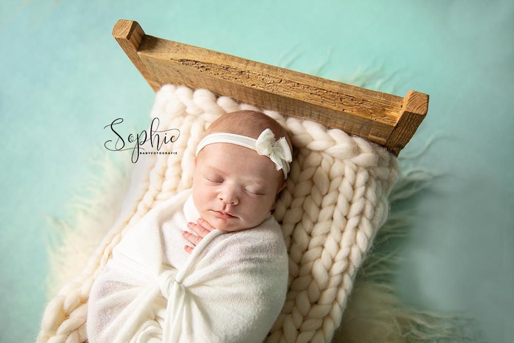 een foto van een newborn in het wit tijdens een newbornshoot in vught